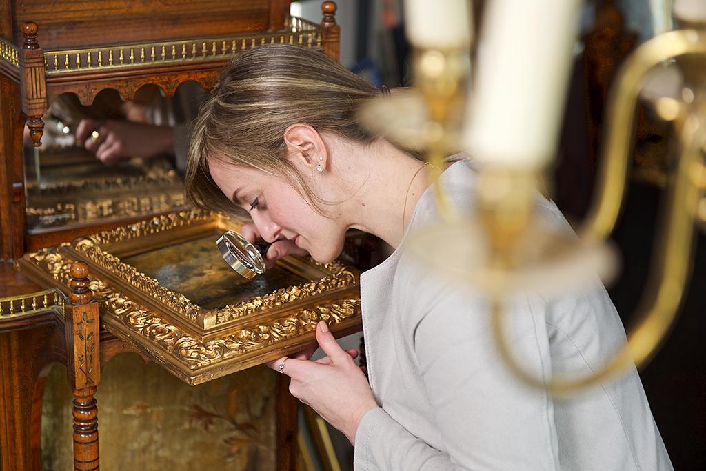 Die Kunsthistorikerin untersucht das Gemälde mit der Lupe