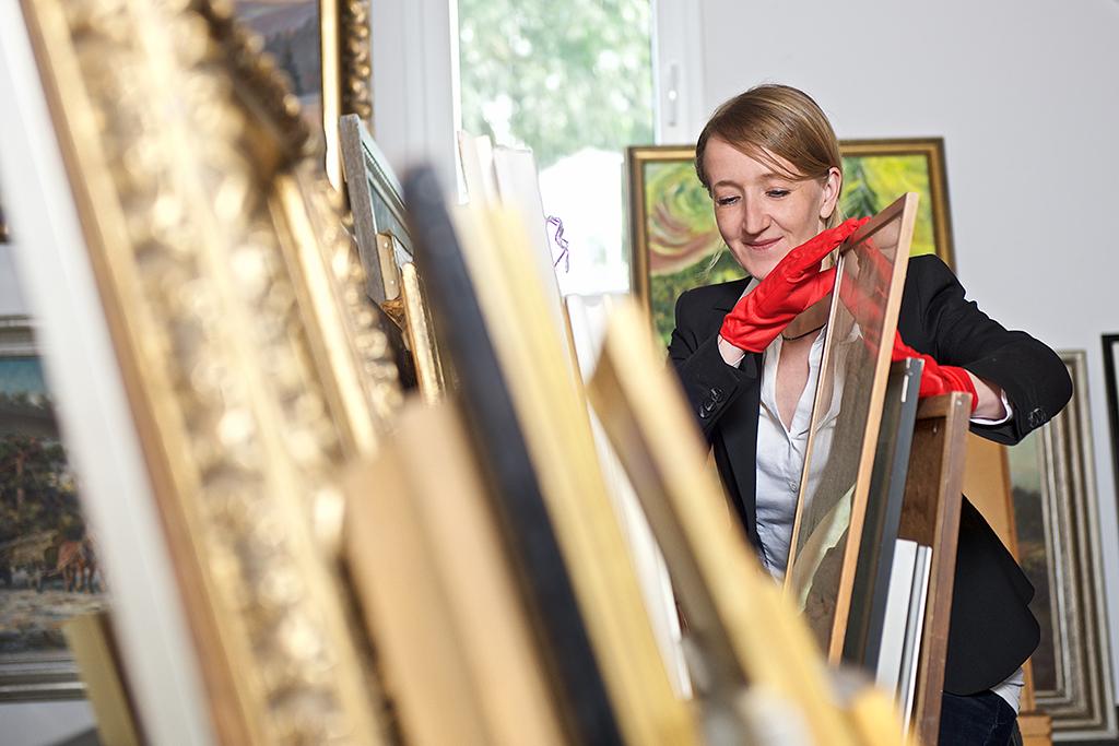 Die Geschäftsführerin trägt rote Handschuhe und begutachtet die eingelieferte Ware - hier Gemälde