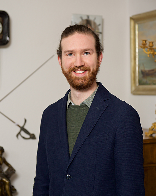 The man in charge of PR and social media wears a blue jacket, antiques can be seen in the background.